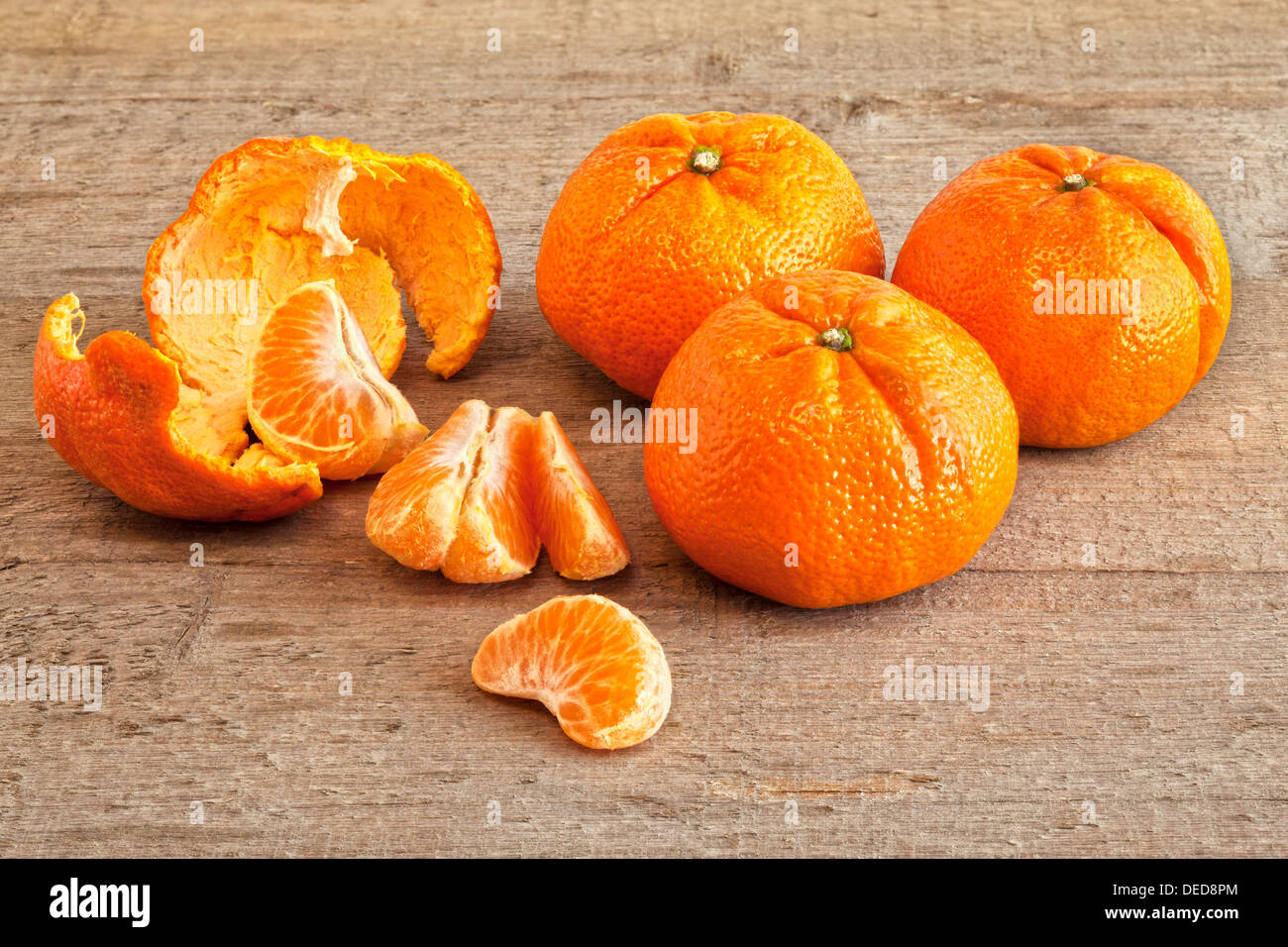 Mandarin Oranges - mandarin oranges on a rustic wooden surface, three whole, one peeled and segmented. - Stock Image