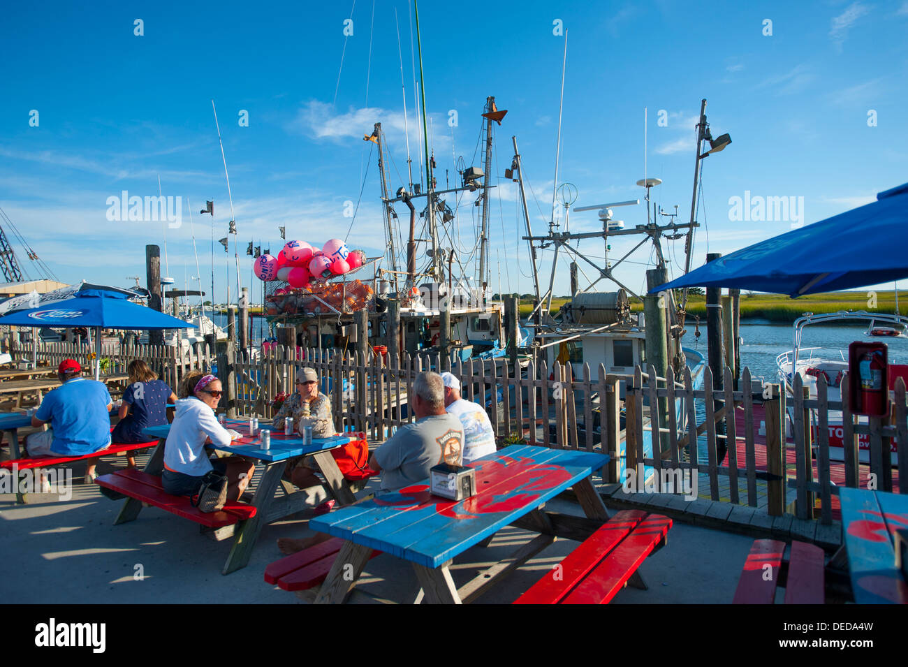 USA, New Jersey NJ Wildwood Hooked Up seafood market and restaurant - dining by the fishing boats outdoors summer - Stock Image