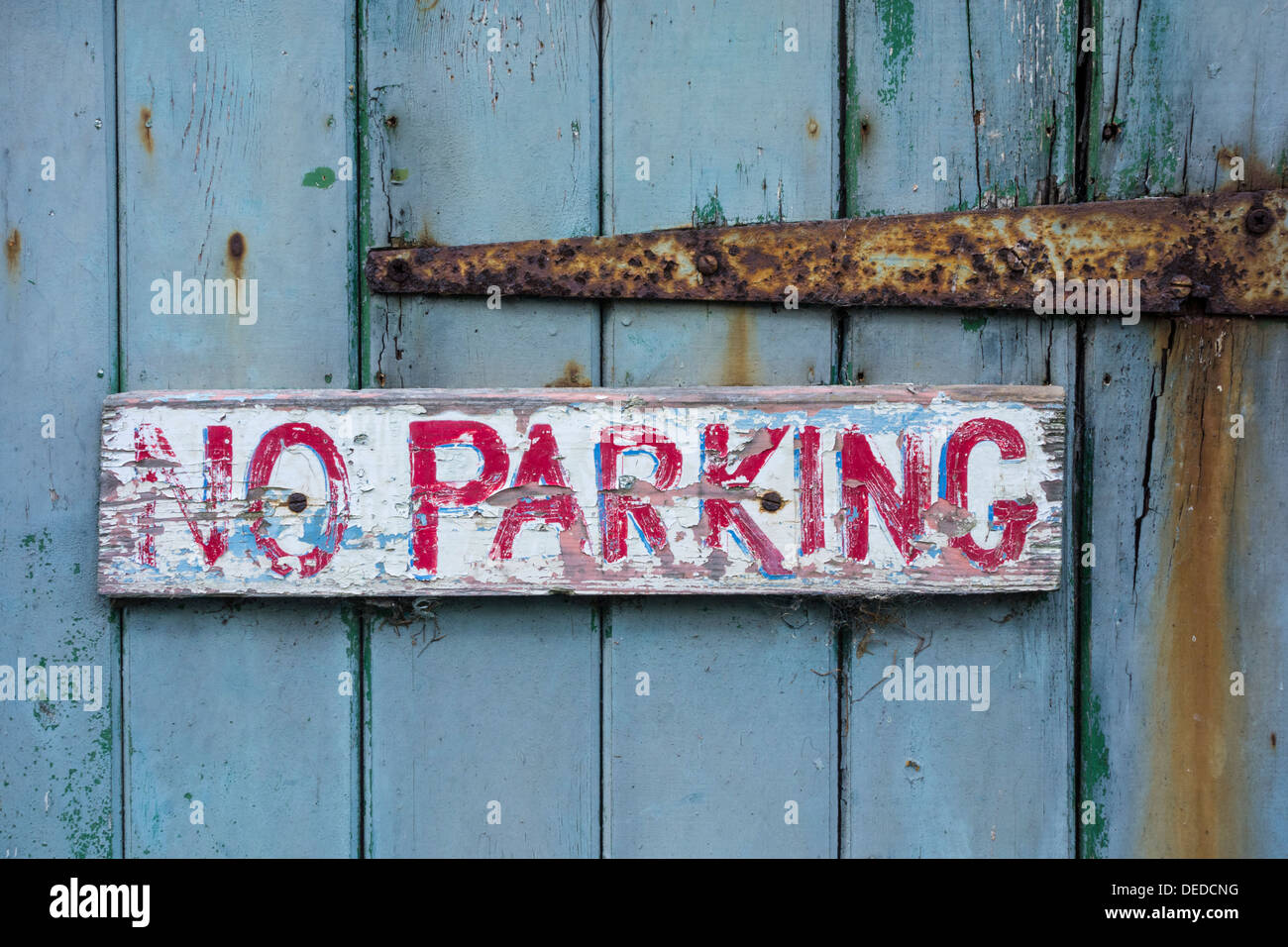 No Parking sign on weathered wooden door - Stock Image