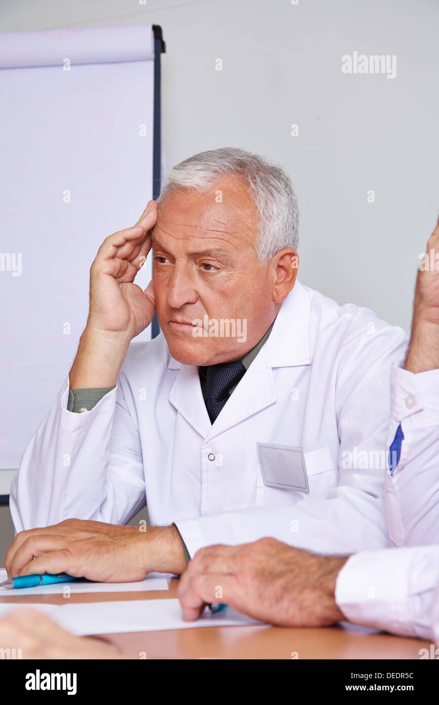 Pensive senior doctor thinking in a team meeting - Stock Image