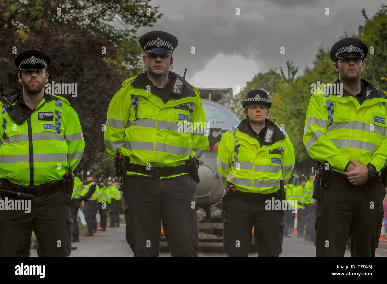 Balcombe, West Sussex, UK. 16th Sept, 2013. Cuadrilla tanker leaves the site surrounded by Police Officers who now outnumber protesters. Protesters lately have not seen to be disrupting Police in their duties and the atmosphere has been very relaxed and amicable.  Environmentalist rejoiced after todays failed attempt by West Sussex County  in the high court, due flawed case, to evict them from the road side camp. © David Burr/Alamy Live News - Stock Image