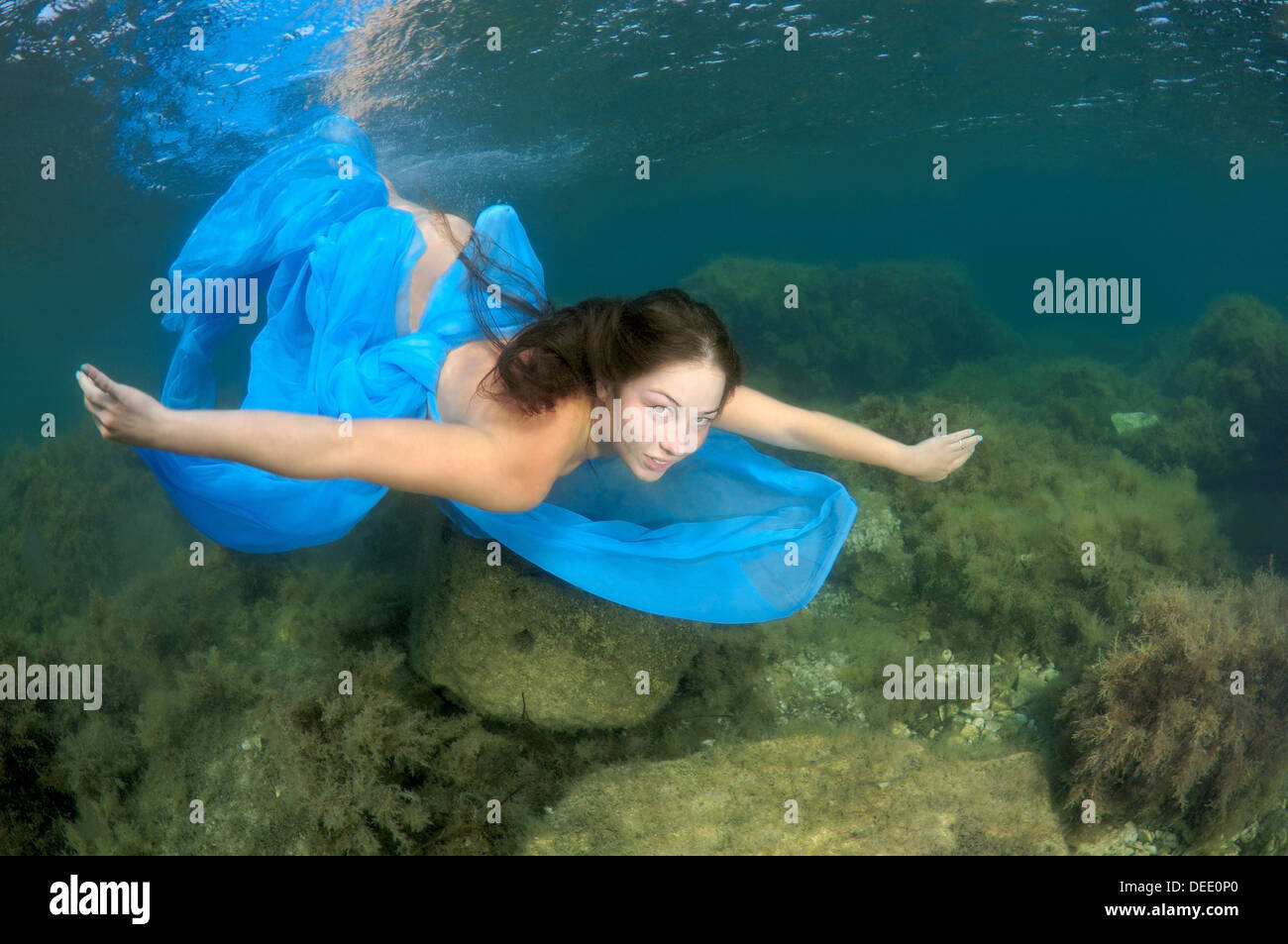 A young woman with long hair in a blue dress dives underwater in Black Sea - Stock Image
