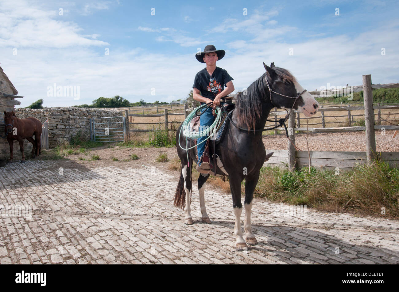 young cowboy sitting on a horse with a lasso - Stock Image