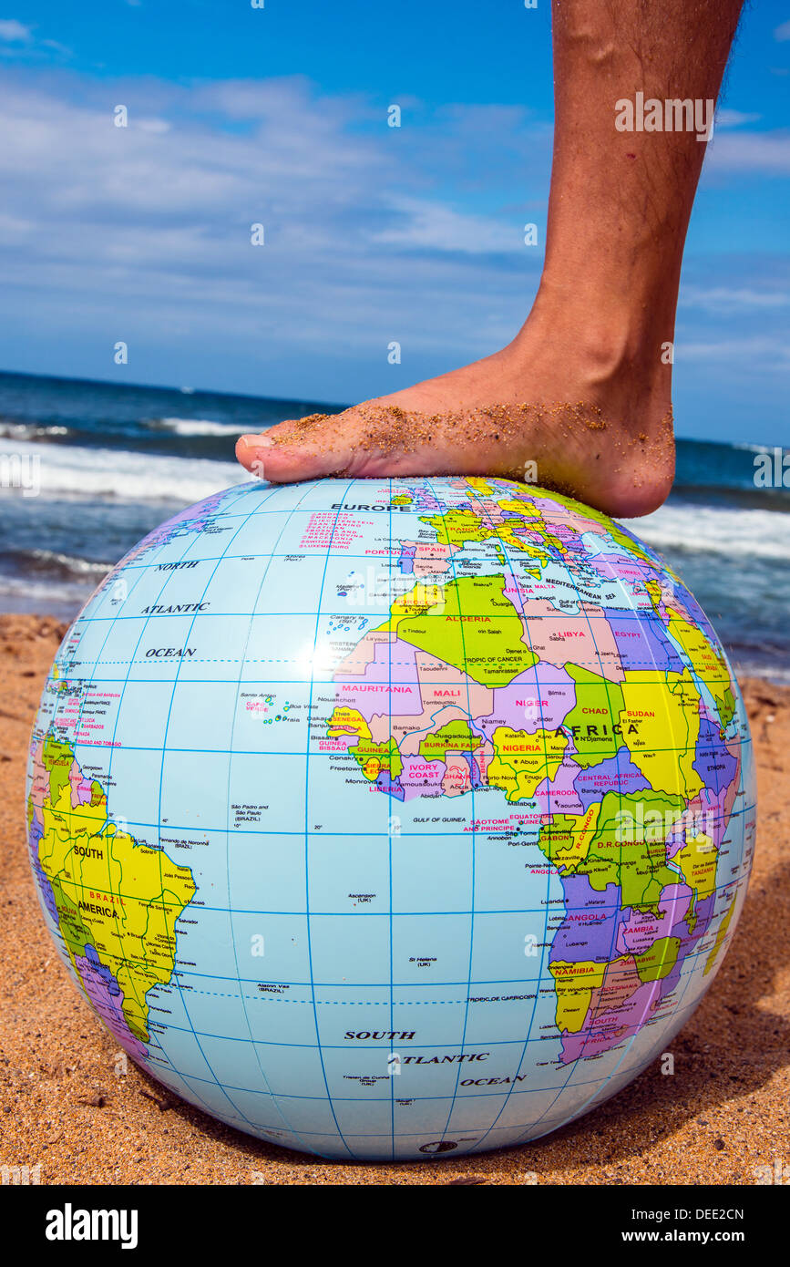 Male foot on an inflatable earth beach ball with sea behind - Stock Image