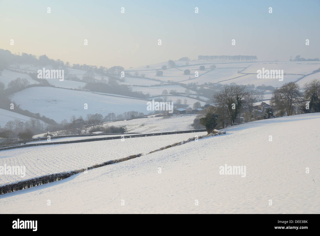 Snow covered hillside pastureland, arable fields and bare trees in winter, Tadwick, Bath and Northeast Somerset, England, UK - Stock Image