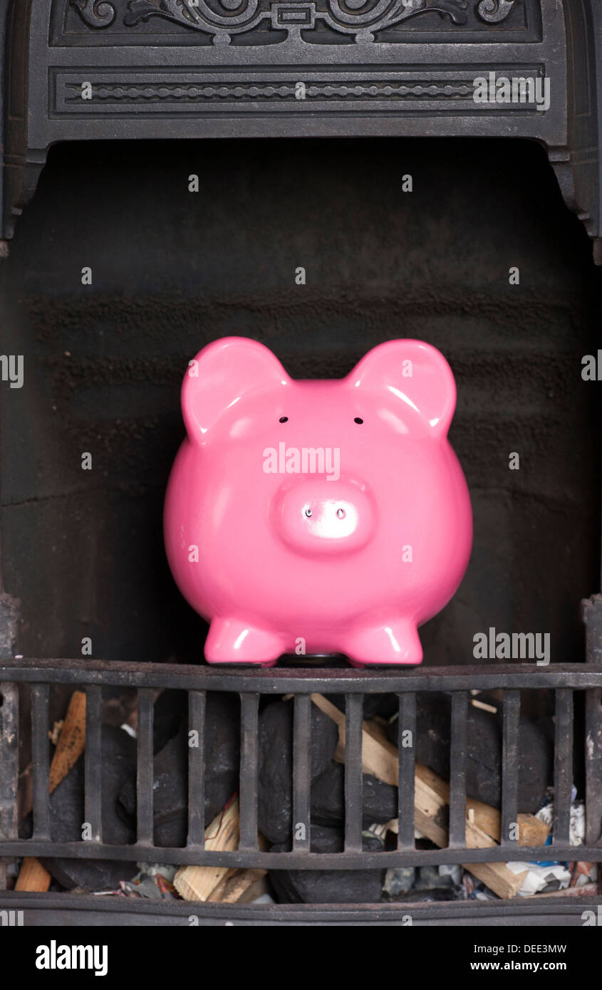 piggy bank in a fire place - Stock Image