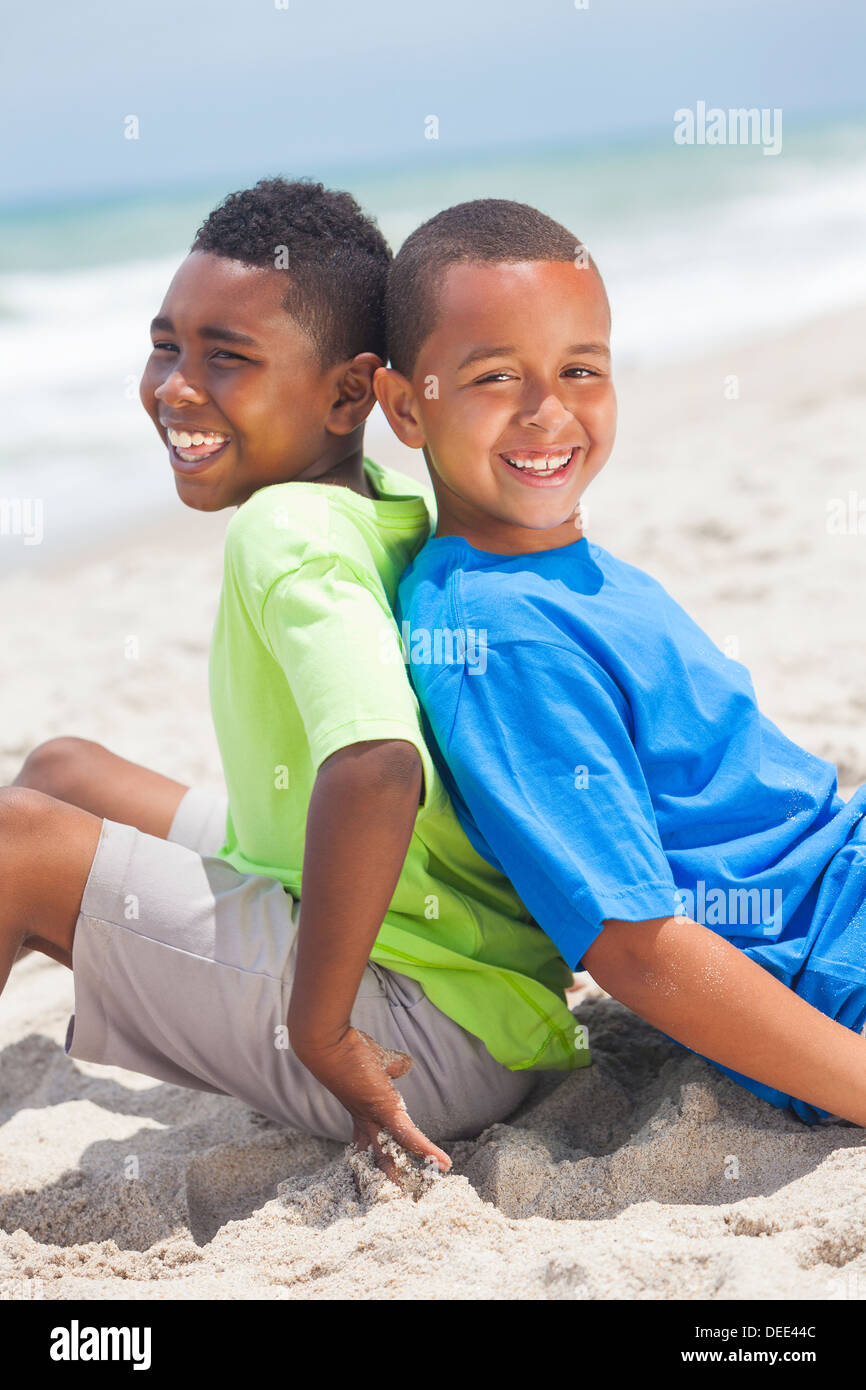 Two young African American boys sitting back to back playing having fun on a sunny beach - Stock Image