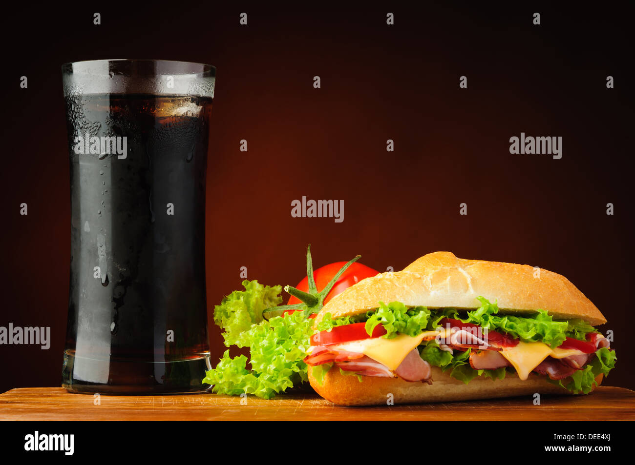 still life with sandwich, vegetables and cola drink - Stock Image