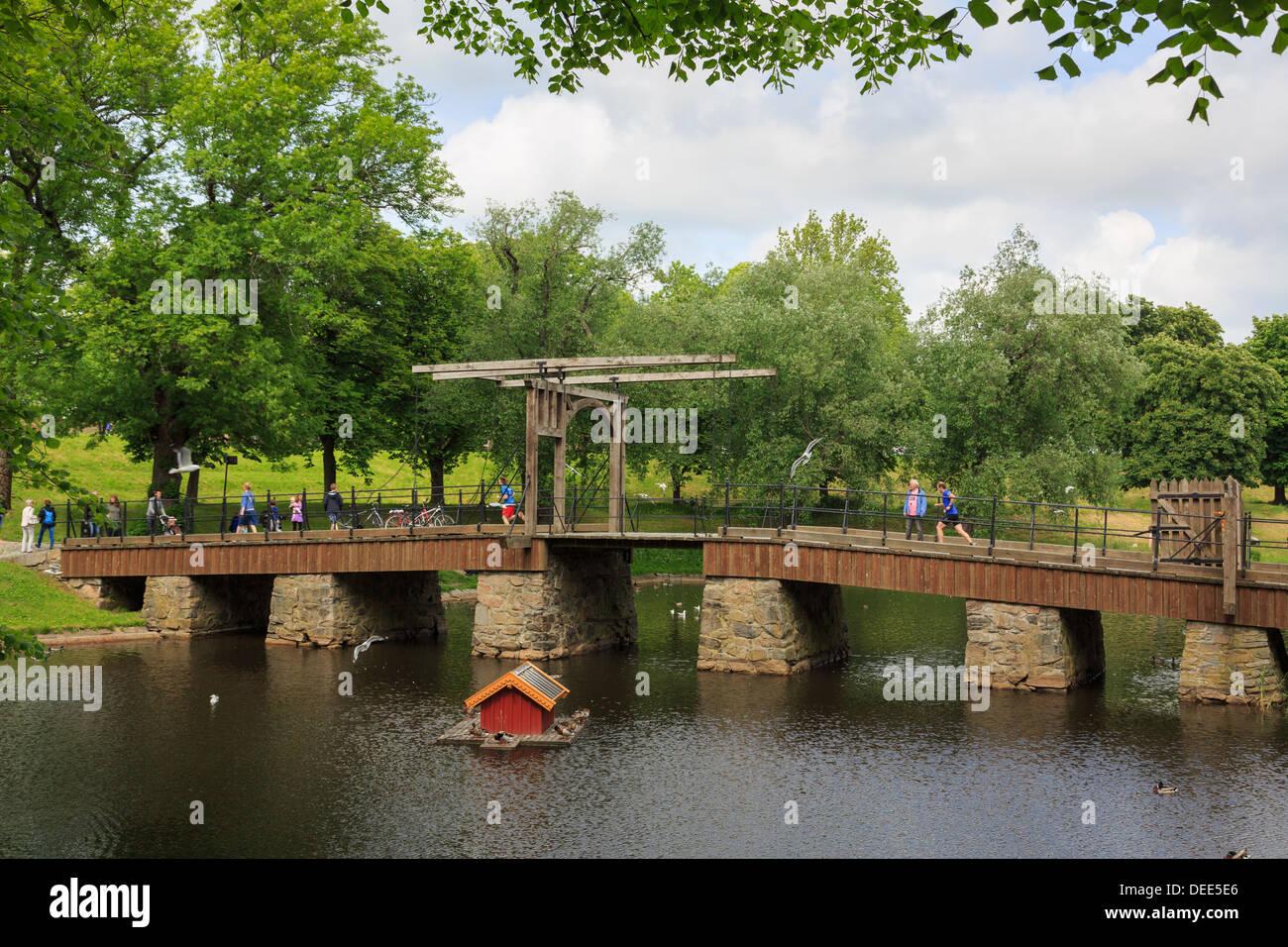 Old wooden drawbridge across the moat around old fortified town of Gamlebyen, Fredrikstad, Ostfold, Norway, Scandinavia - Stock Image