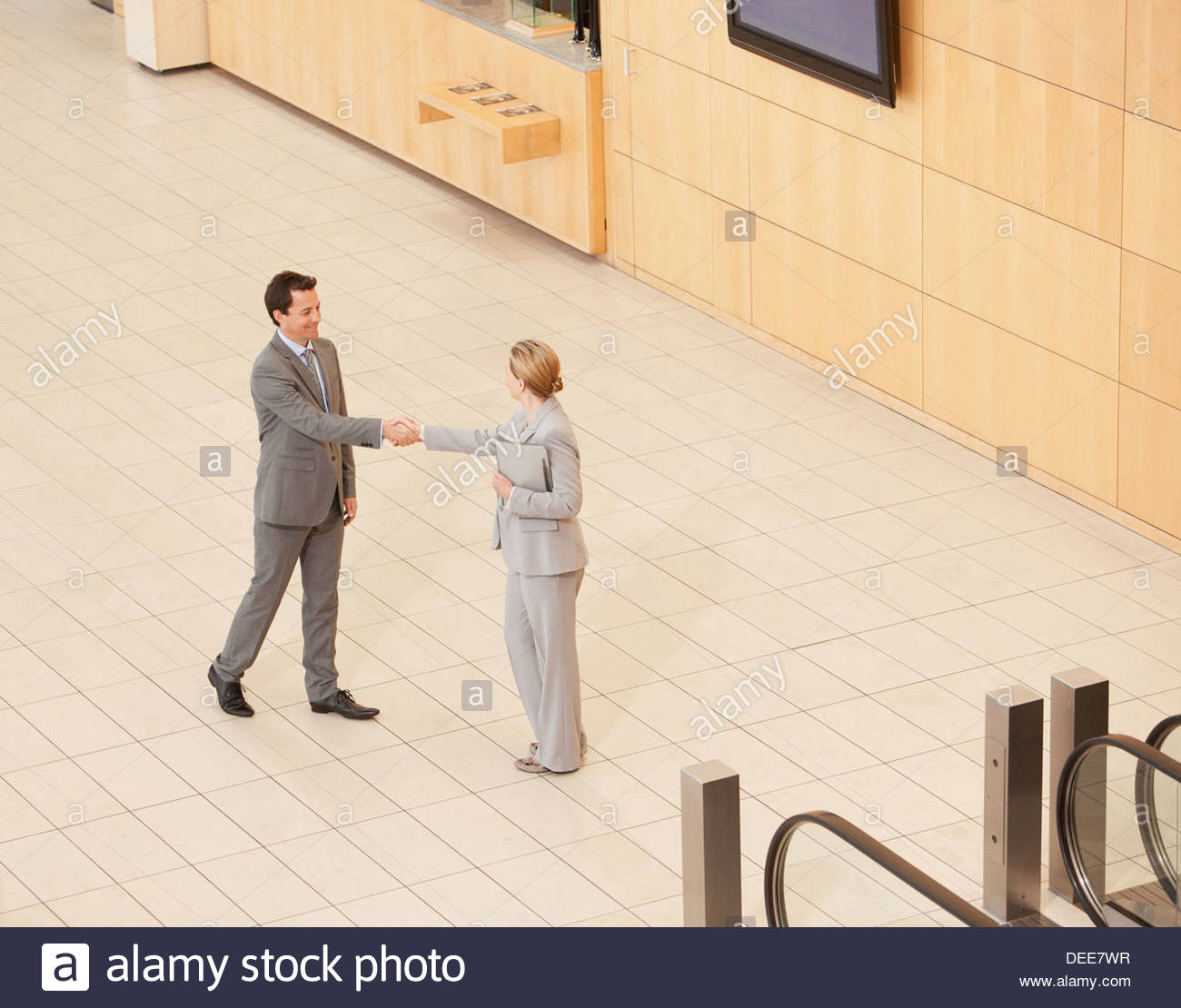 Business people standing at bottom of escalator - Stock Image