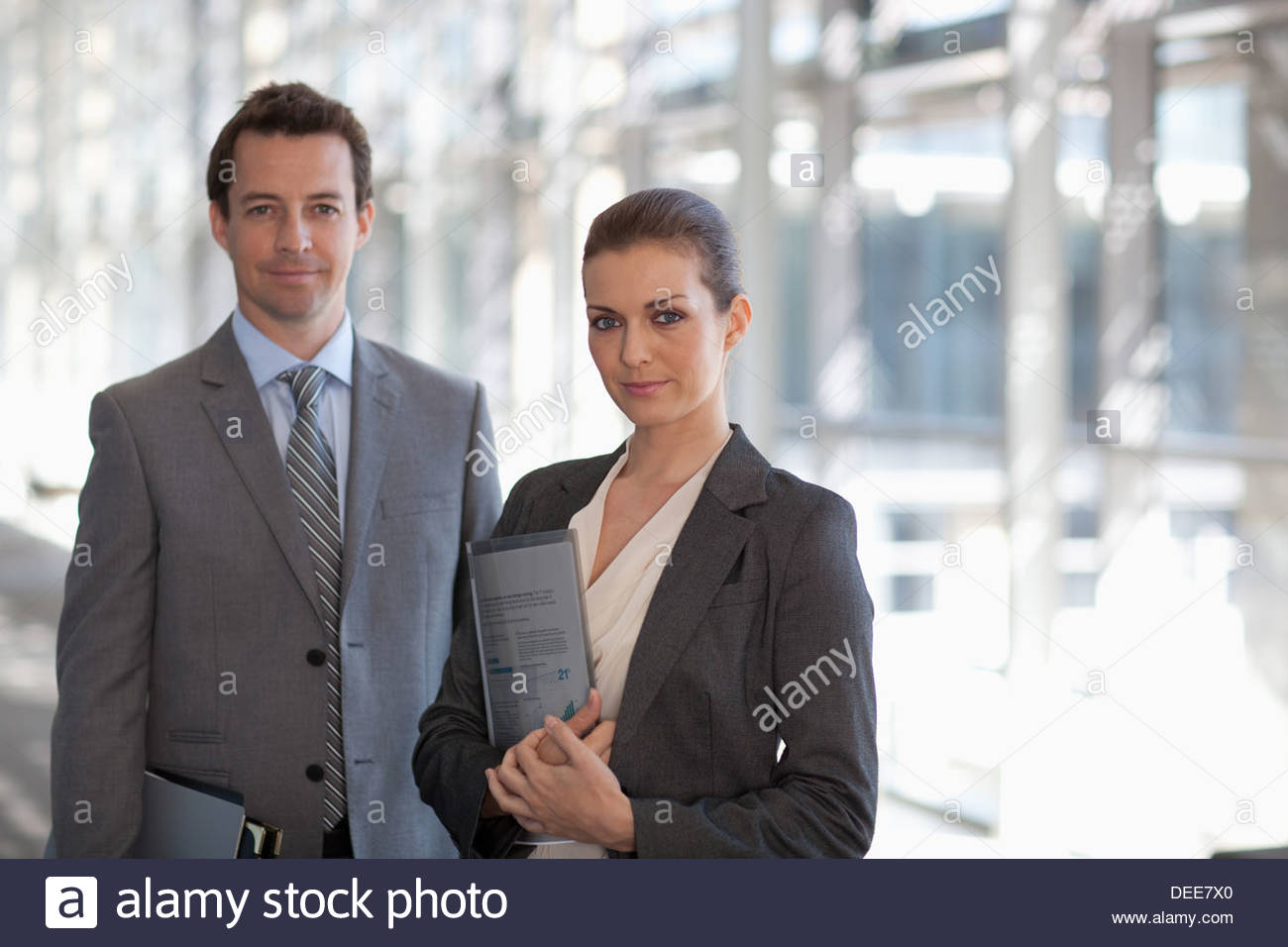 Portrait of smiling businessman and businesswoman in corridor - Stock Image