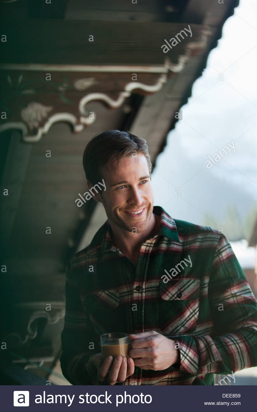 Smiling man drinking coffee on cabin porch - Stock Image