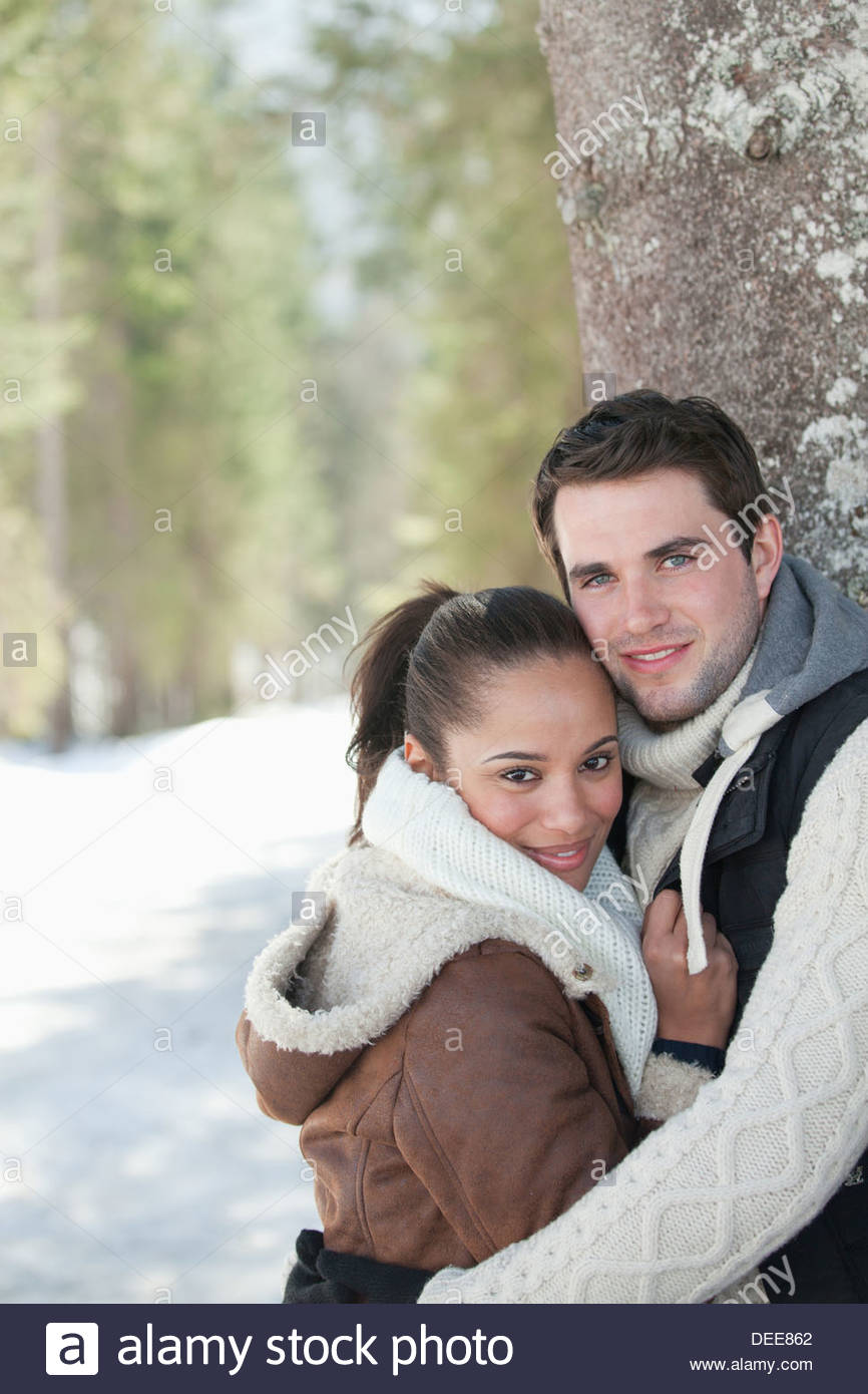 Portrait of smiling couple leaning against tree trunk in snowy woods - Stock Image