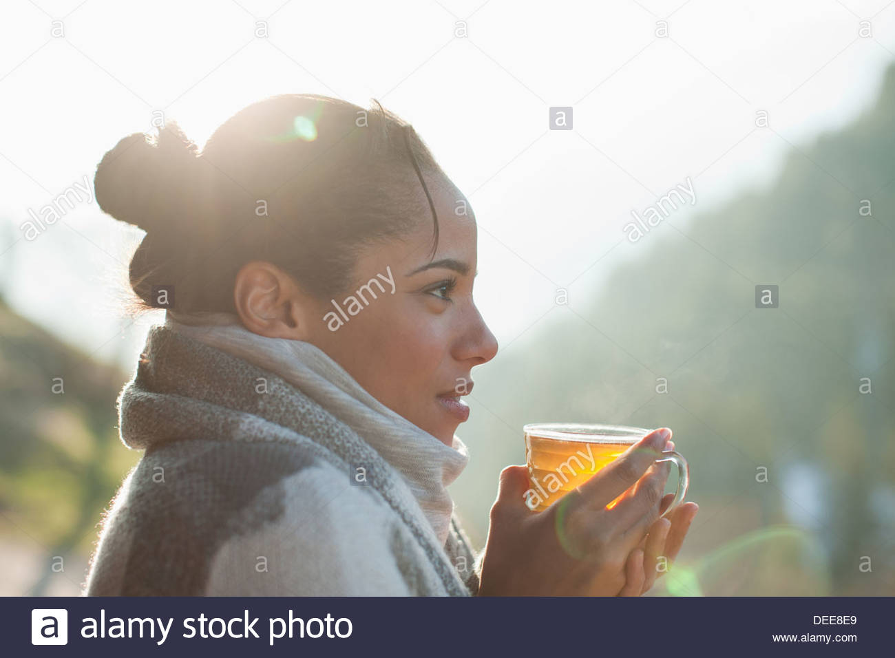 Close up of smiling woman drinking tea outdoors - Stock Image