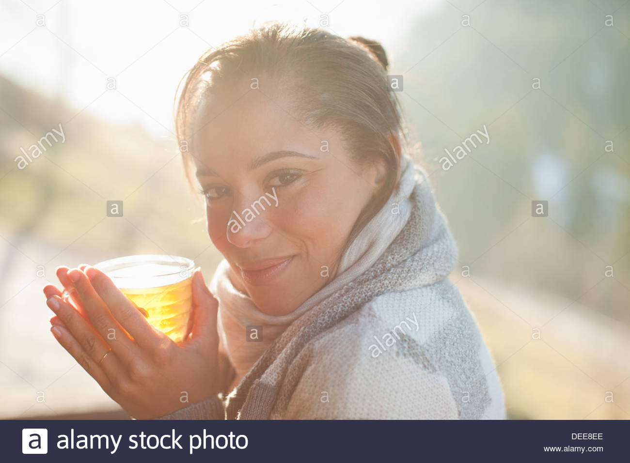 Portrait of smiling woman in scarf drinking cider - Stock Image