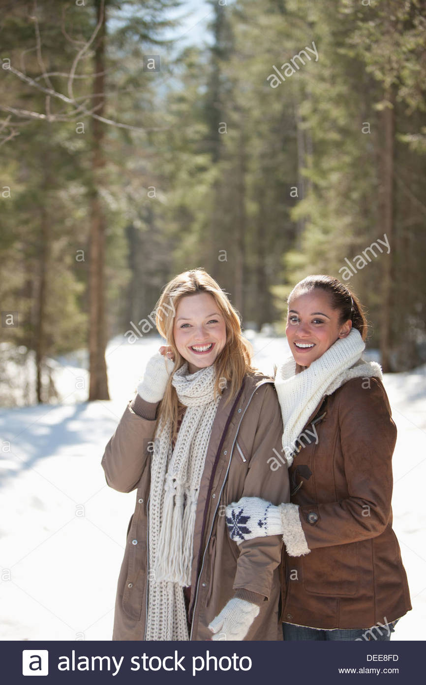 Portrait of smiling friends hugging in snowy woods - Stock Image