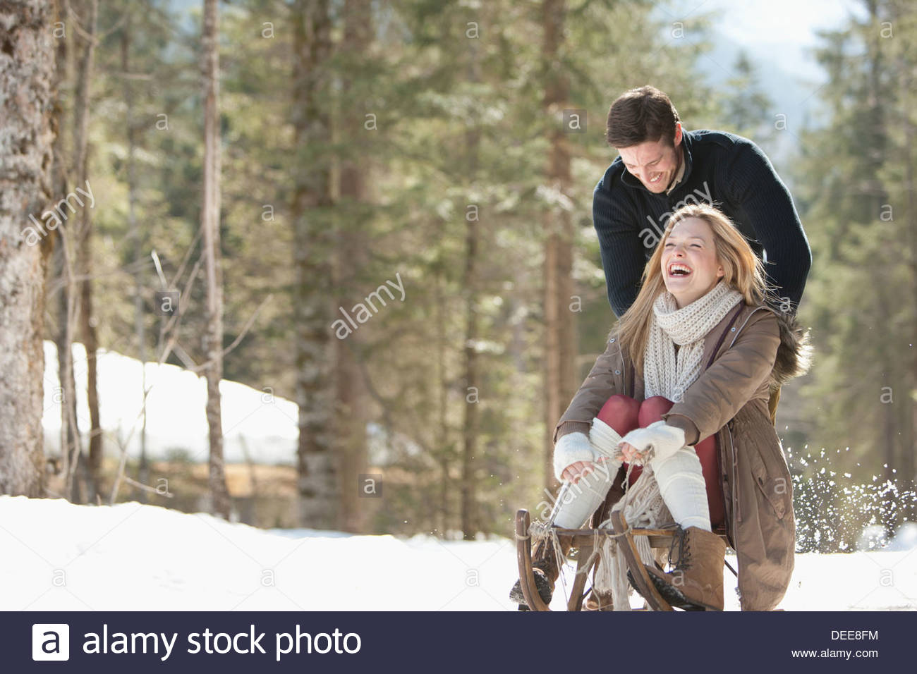 Man pushing woman on sled in snowy woods - Stock Image