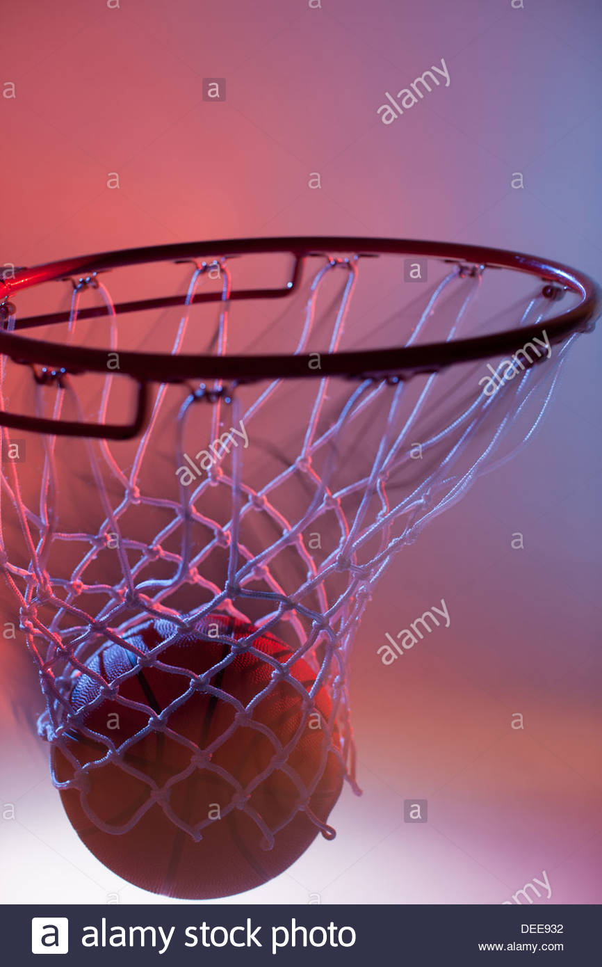 Blurred view of basketball going into hoop - Stock Image