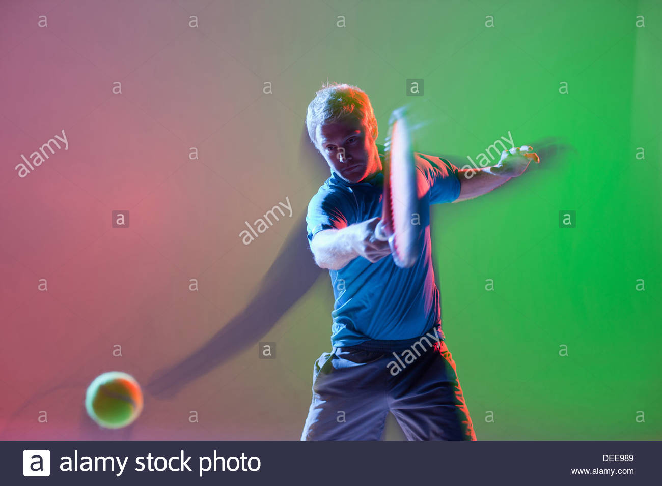 Blurred view of tennis player swinging racket - Stock Image