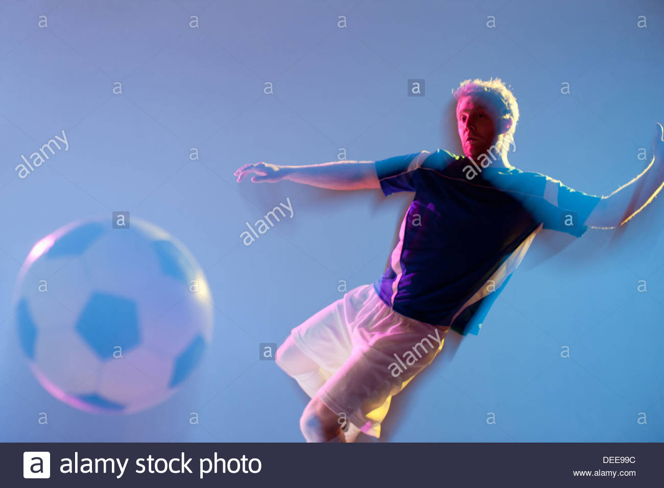Blurred view of soccer player kicking ball - Stock Image