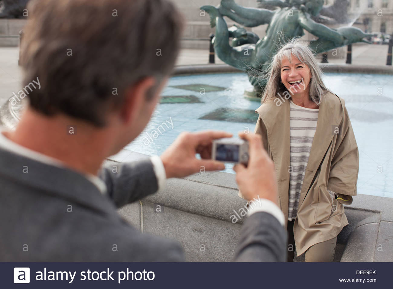 Man with digital camera photographing woman near fountain - Stock Image