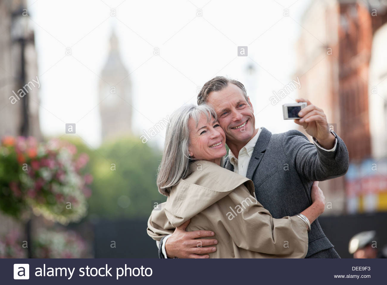 Couple taking self-portrait with digital camera in city - Stock Image