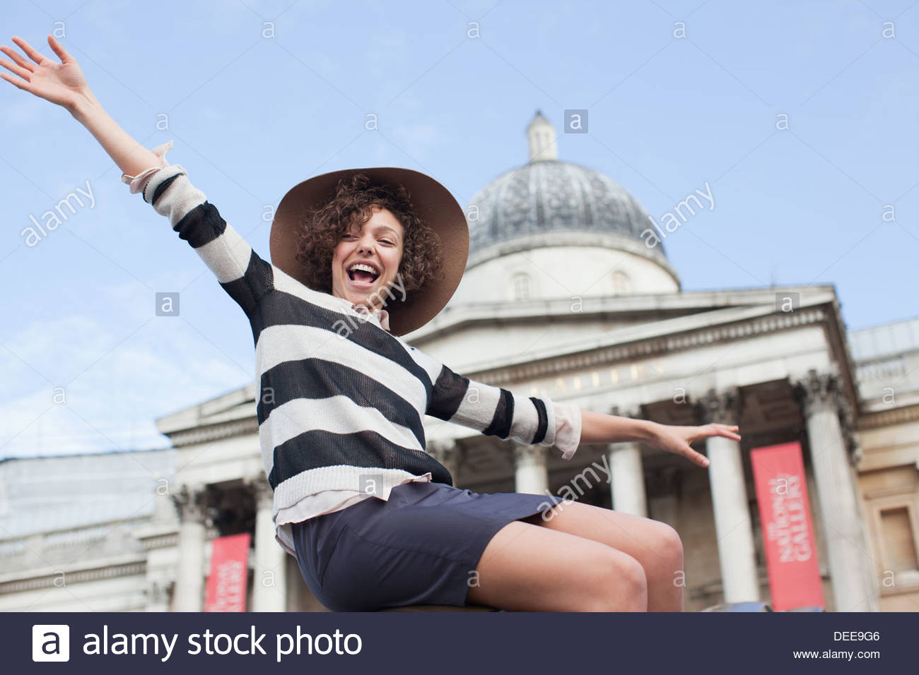 Exuberant woman in hat below historical landmark in London - Stock Image