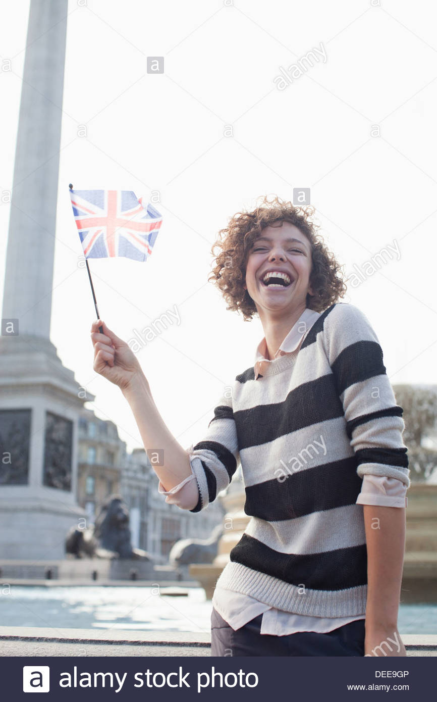 Happy woman holding British flag - Stock Image