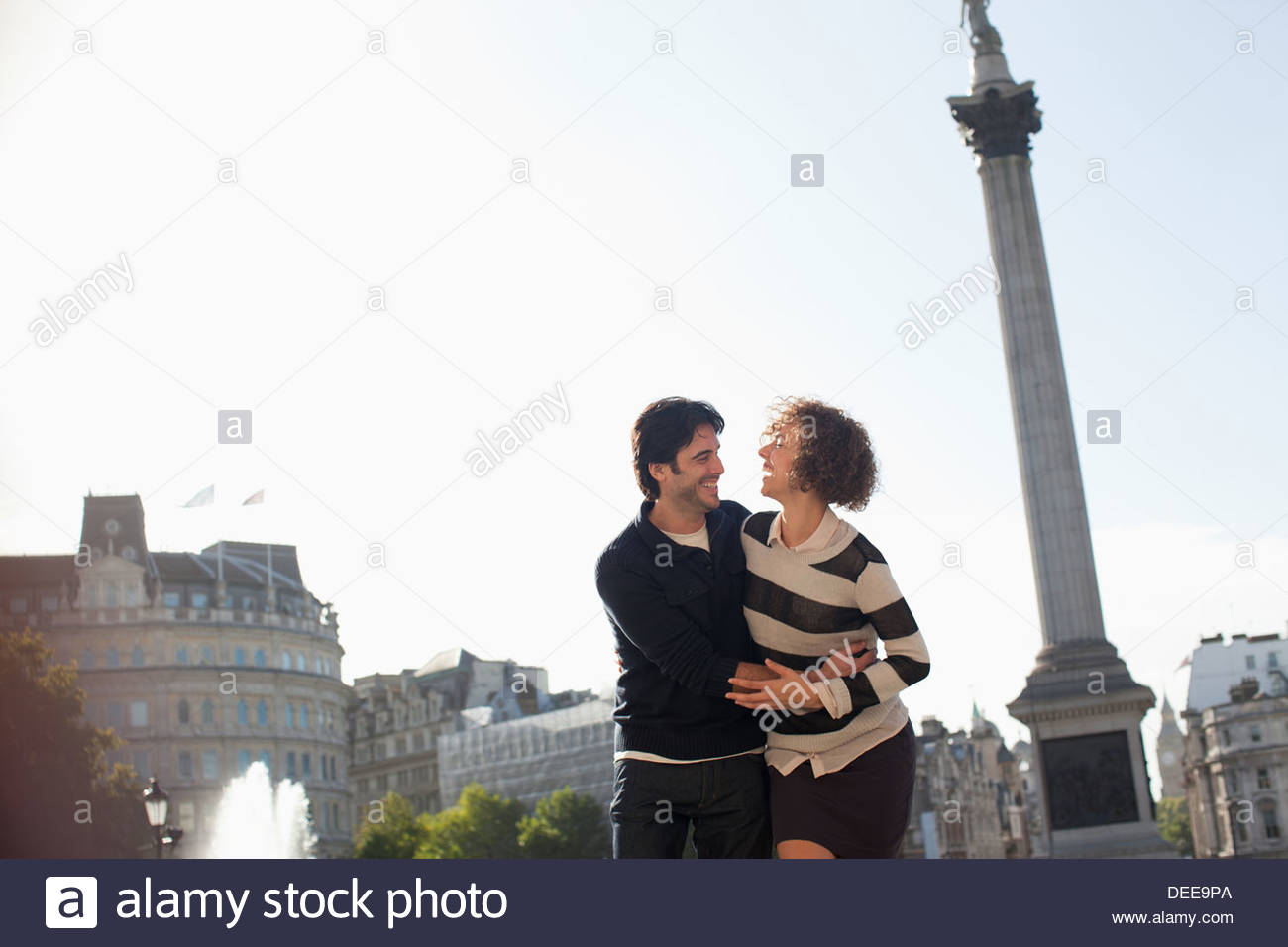 Couple hugging under monument in London - Stock Image