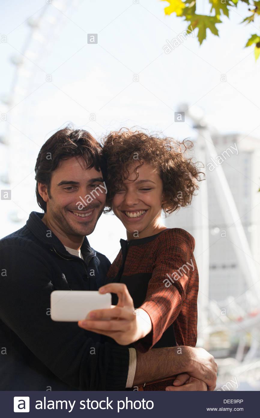 Couple taking self-portrait with digital camera below ferris wheel - Stock Image