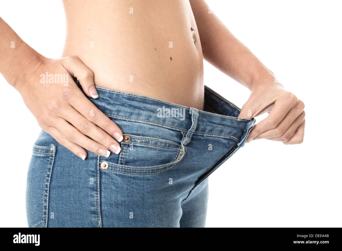 Model Released. Attractive Young Woman Showing Weight Loss - Stock Image