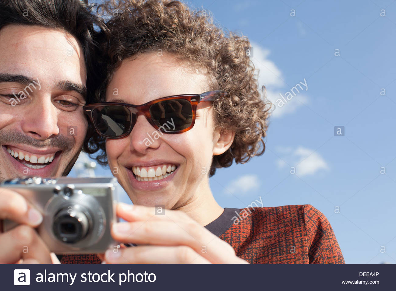Happy couple taking self-portrait with digital camera in front - Stock Image