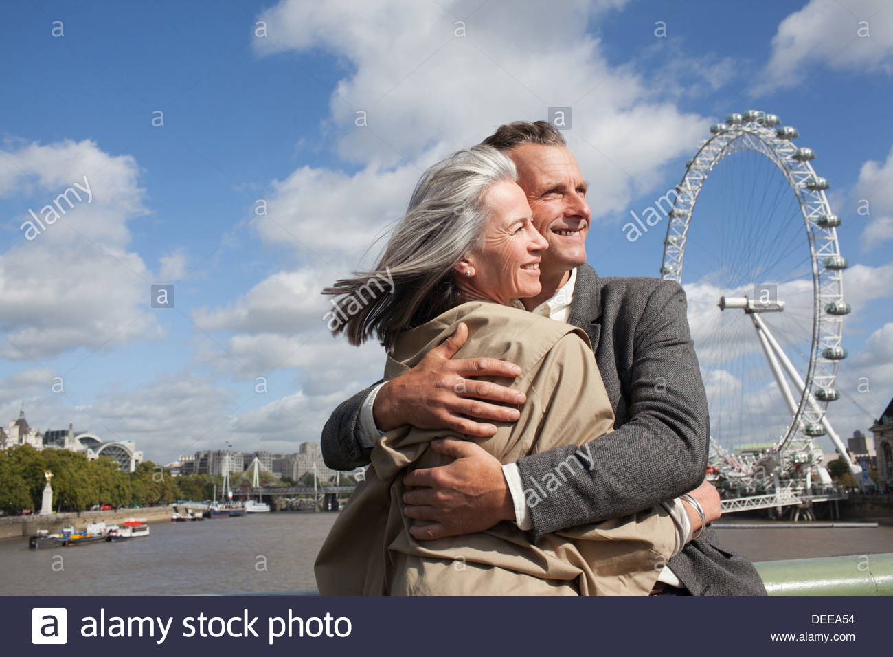 Portrait of smiling couple hugging in front of Thames river - Stock Image