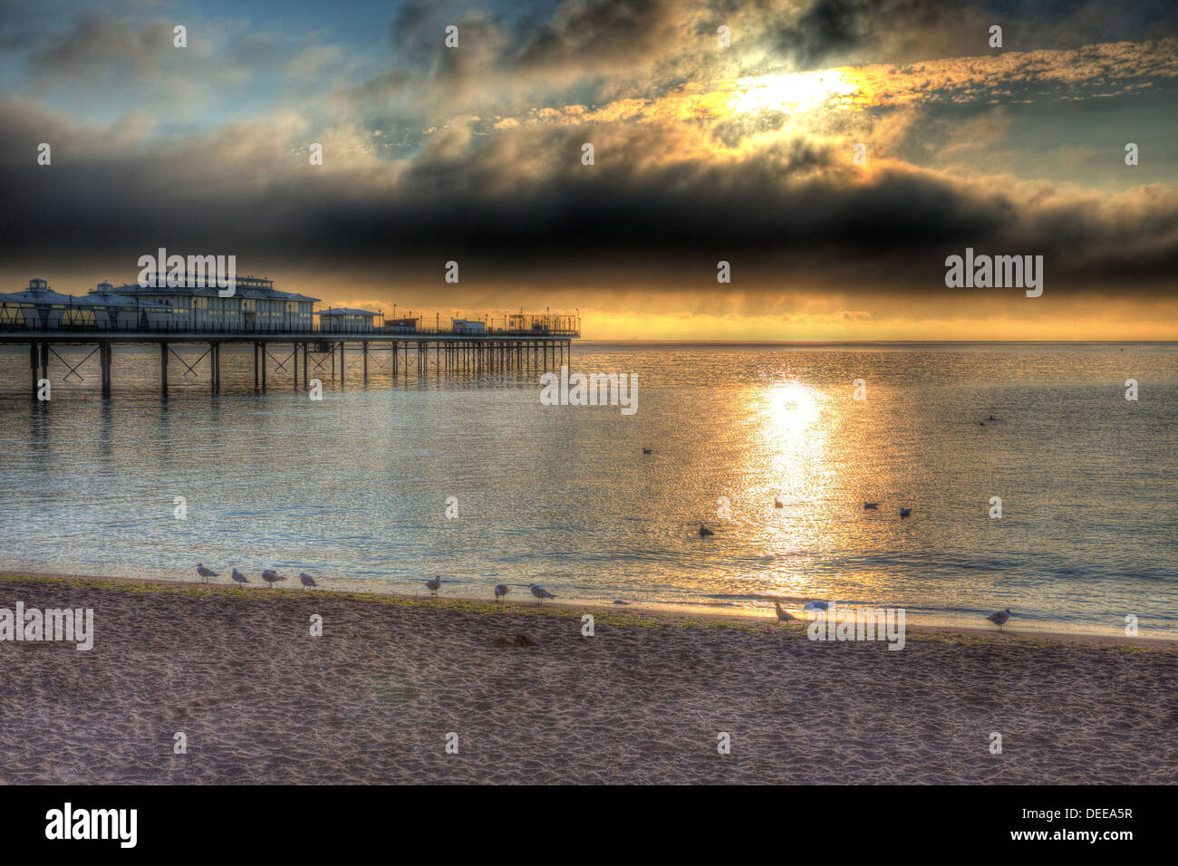 Pier with dramatic dark sky and moody clouds and sunlight in HDR - Stock Image