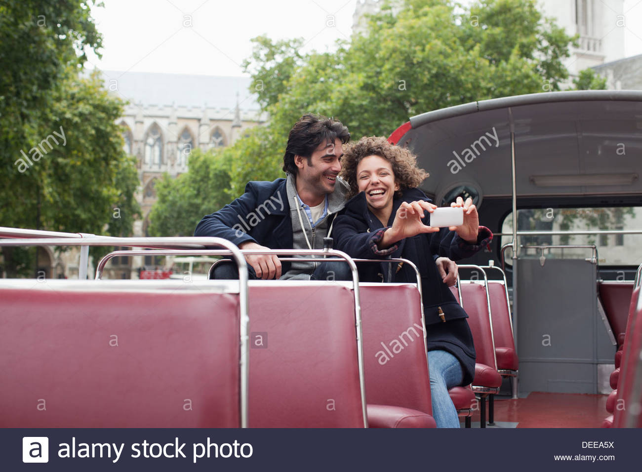 Couple with digital camera riding double decker bus near Big Ben clocktower in London - Stock Image
