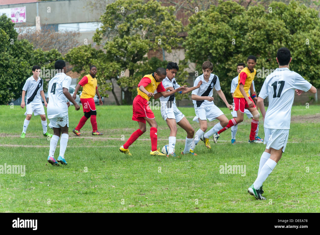 Junior football player tackled by defenders, Cape Town, South Africa - Stock Image