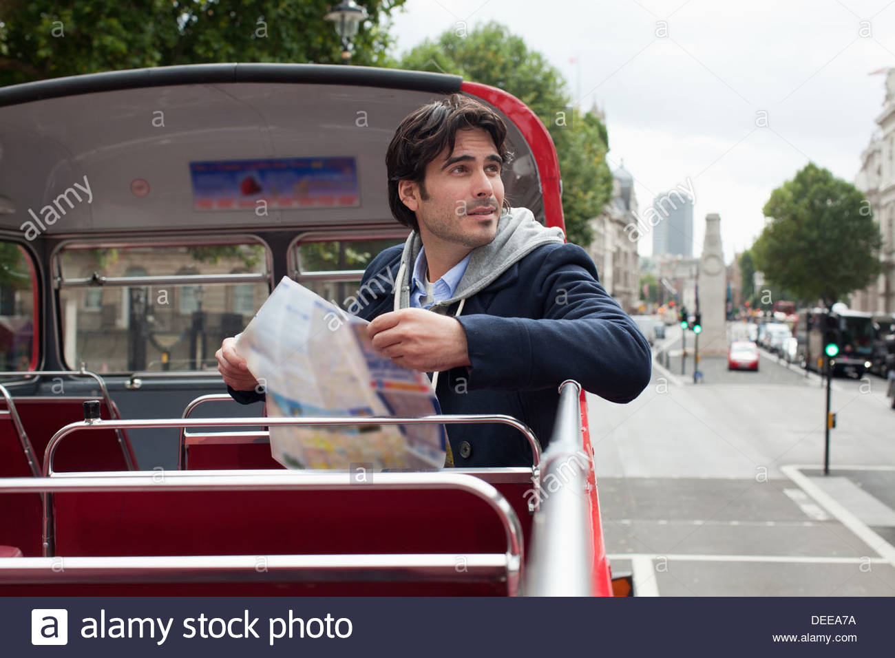 Man with map on double decker bus - Stock Image