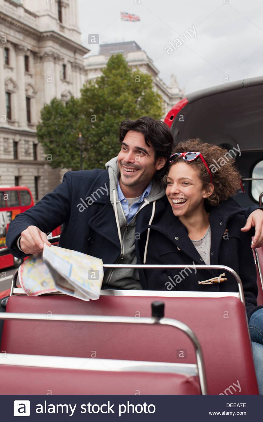 Couple riding double decker bus past Big Ben clocktower in London - Stock Image