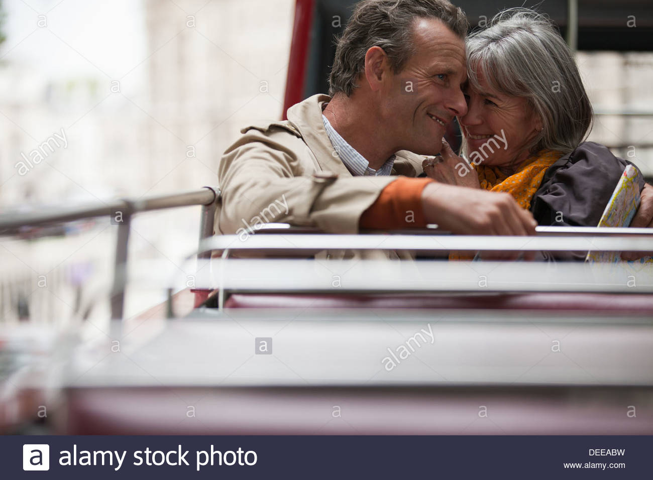 Smiling senior couple on double decker bus in London - Stock Image