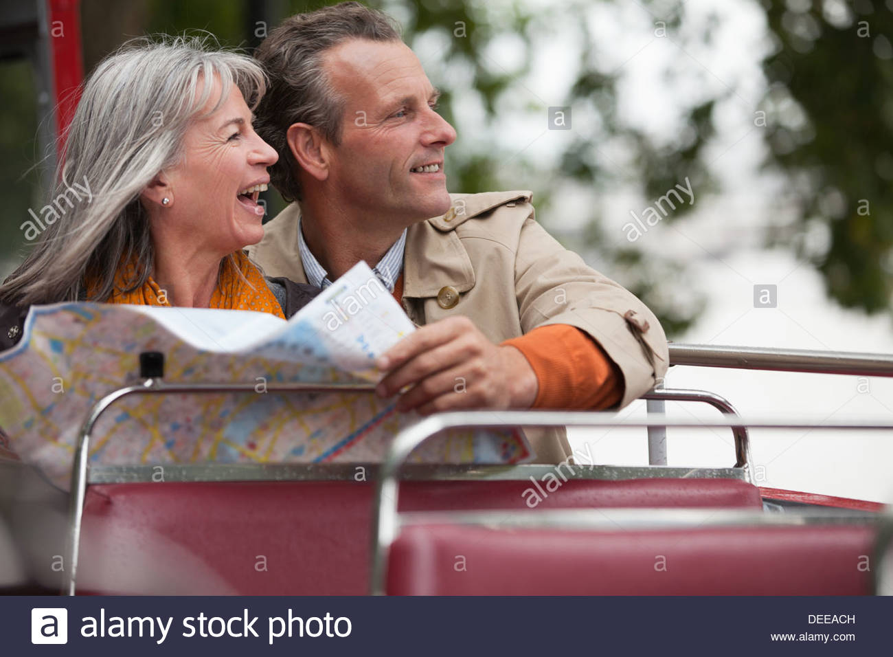 Smiling couple looking at map on double decker bus - Stock Image