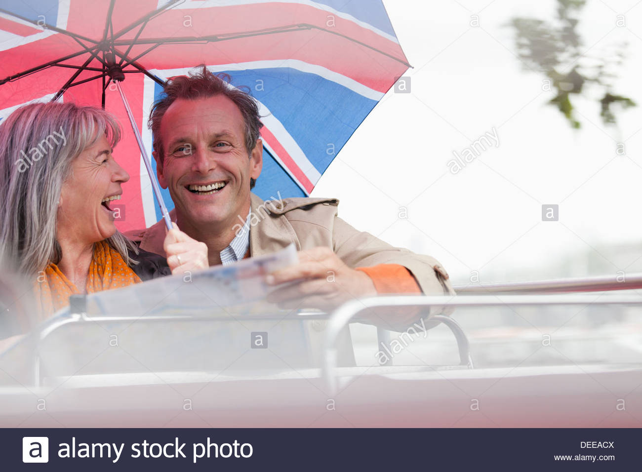 Happy couple with British flag umbrella riding double decker bus - Stock Image