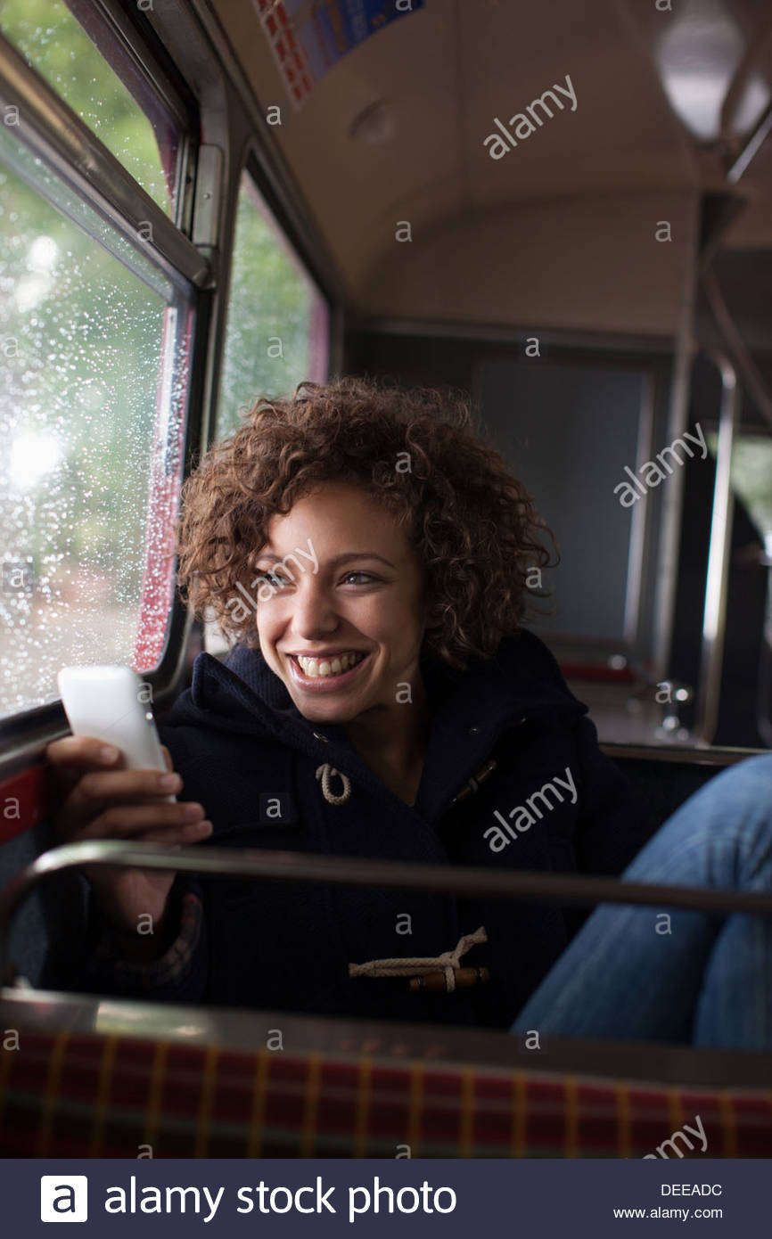Smiling woman using cell phone on bus - Stock Image