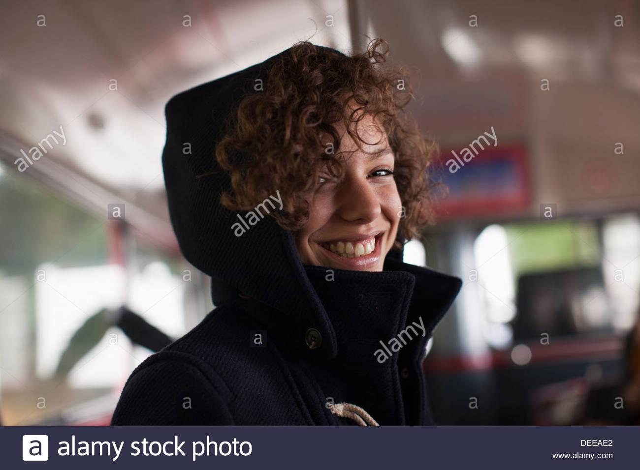 Smiling woman riding bus - Stock Image