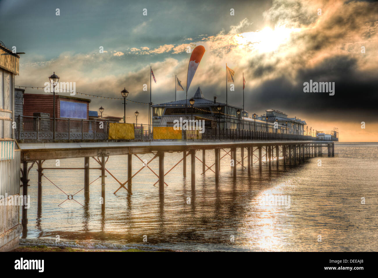 English Pier with dramatic sky and moody clouds and sunlight in HDR - Stock Image