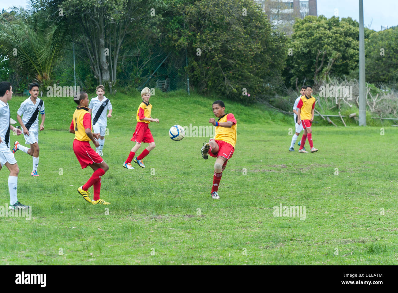 Junior football player volleys the ball , Cape Town, South Africa - Stock Image