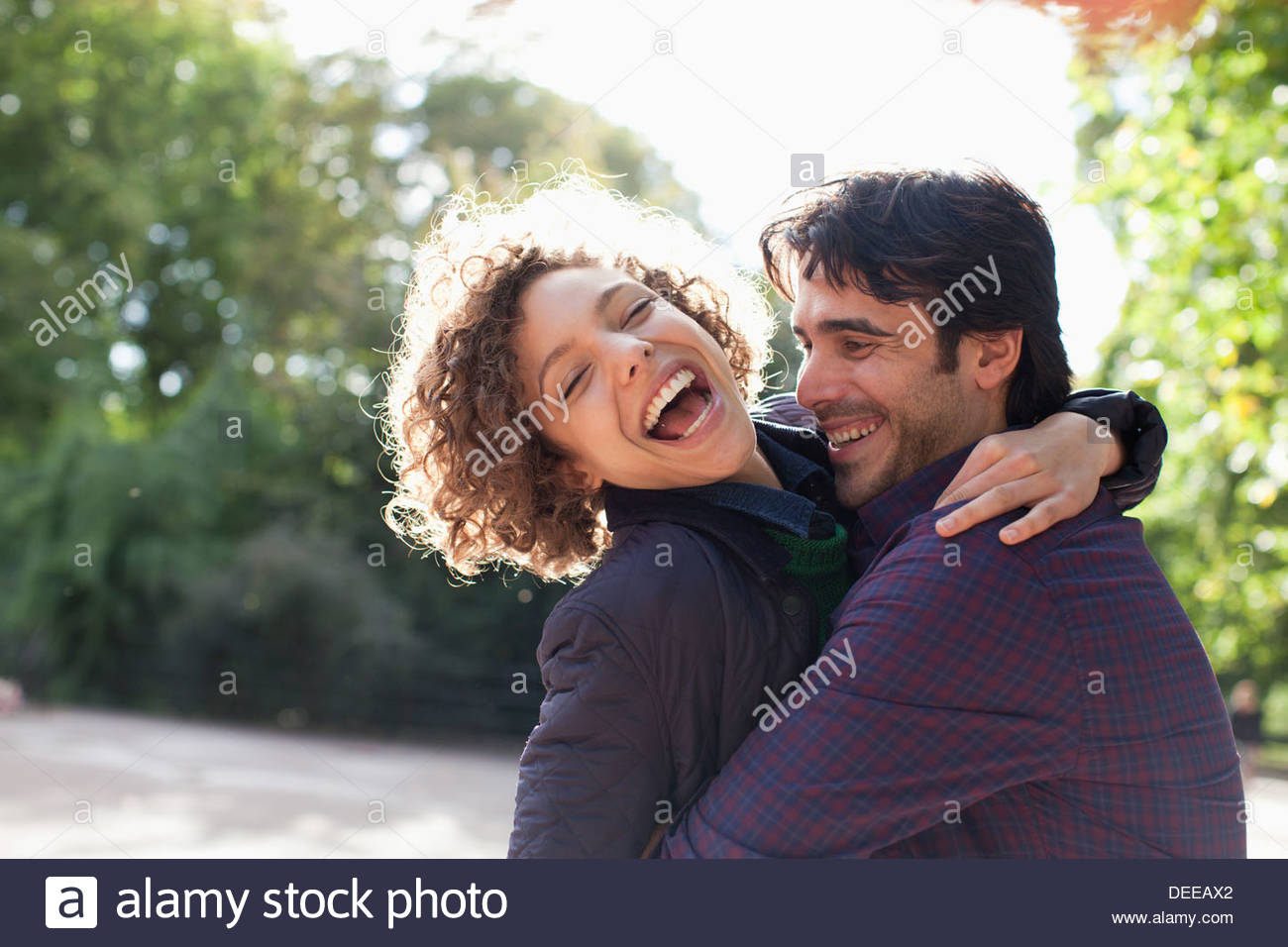 Sun shining behind happy couple hugging - Stock Image