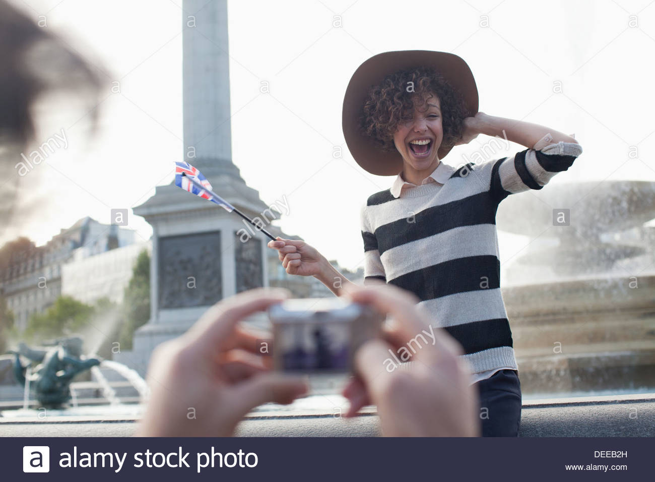 Man with digital camera taking photograph of happy woman with British flag in front of fountain - Stock Image