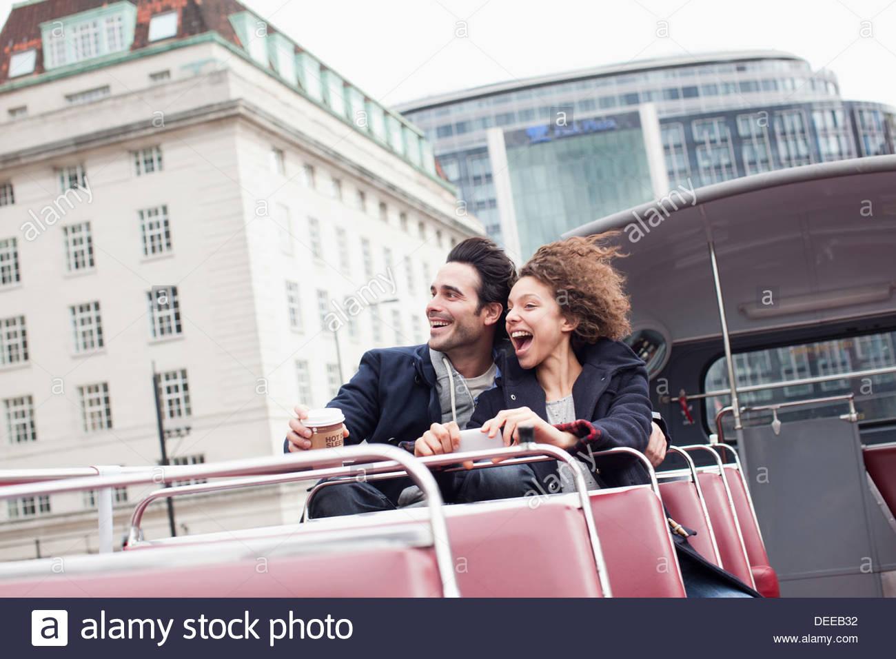Exuberant couple riding double decker bus in London - Stock Image