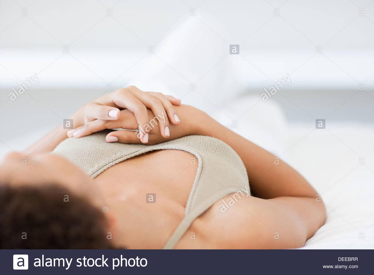 Woman laying on bed praying - Stock Image