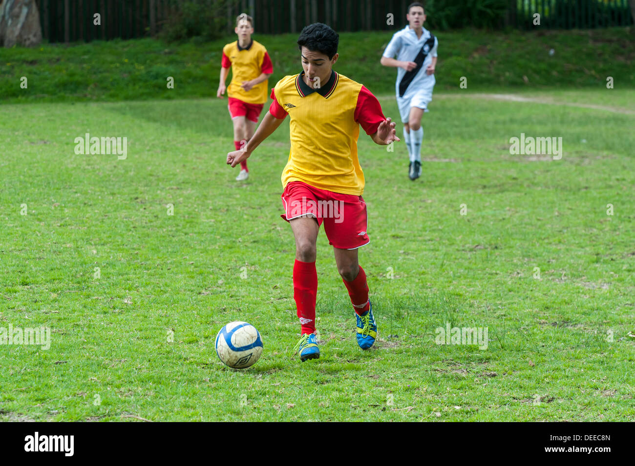 Junior football player running with the ball, Cape Town, South Africa - Stock Image